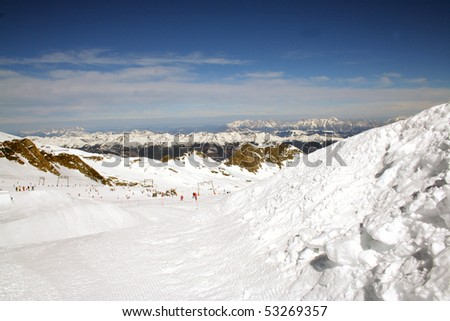 Scenic view of skiers on snowy Alpine slope.