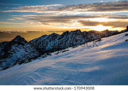 Scenic view of snowy winter mountains and colorful sunset, Rysy - High Tatras, Slovakia - stock photo