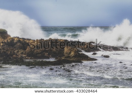 Scenic view of strong waves crashing on rocks.