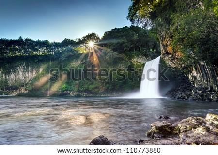 Scenic view of sunrise on Bassin la Paix waterfall - Reunion Island. - stock photo