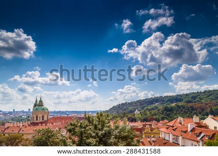 Scenic view of the historical center of Prague: the glorietta of the US embassy with american flag and view of old town with the characteristic and picturesque red rooftops and multi-coloured walls. - stock photo