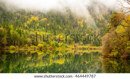 Scenic view of the lake with reflection among colorful fall forest in the morning at Jiuzhaigou nature reserve (Jiuzhai Valley National Park), China.
