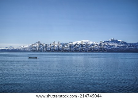 Scenic view of the mountains and a boat in a fjord in Tromso, Norway