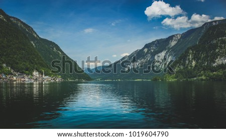 Scenic view of the picturesque Hallstatt lakeside village at the base of a tall Alpine mountain on a sunny day with reflections in the water, Hallstatt, Austria