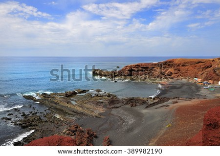 Scenic view on seashore with reef. Waves covered with foam. - stock photo