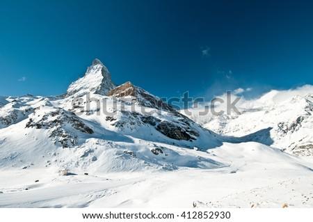 Scenic view on snowy Matterhorn peak on blue sky background in sunny day, Switzerland. - stock photo