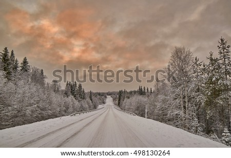 Scenic warm color Sunset over Finnish Road after snow storm blizzard