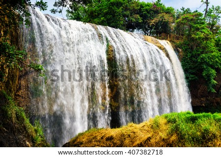 Scenic waterfall with crystal clear water among green woods on blue sky background in Vietnam. Beautiful summer sunny forest landscape. The Elephant waterfall is a popular tourist destination of Asia. - stock photo