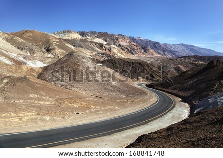 Scenic winding road through colorful desert mountains in Death Valley National Park - stock photo