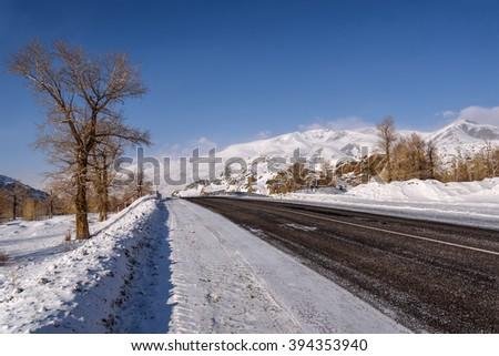 Scenic winter view from the asphalt road in the mountains covered with snow and trees on the side of the road on a background of blue sky and clouds - stock photo