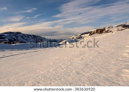 Scenic winter view on the mountains covered with snow on a background of blue sky and beautiful clouds - stock photo