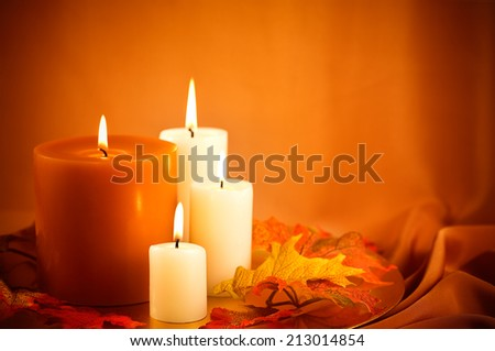 Scented candles against golden background and silk fall leaves.   - stock photo