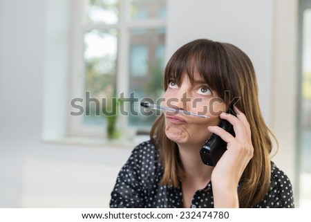 Sceptical businesswoman pulling a thoughtful rueful expression sitting talking on a phone in the office, close up view - stock photo