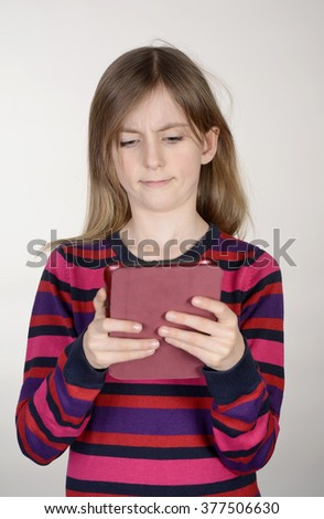 sceptical little girl with digital tablet - stock photo