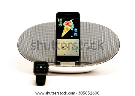 SCHARNHAUSEN, GERMANY - AUGUST 08, 2015: Front view of an Apple iPhone 6 in a Philips docking station and speaker displaying the new Apple Music and being controlled by an Apple watch in the - stock photo