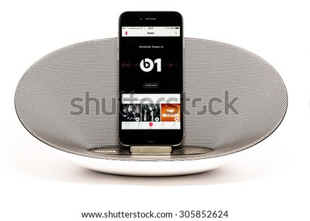 SCHARNHAUSEN, GERMANY - AUGUST 08, 2015: Front view of an Apple iPhone 6 in a Philips docking station and speaker displaying the radio start screen of the new Apple Music with reflection on a white - stock photo