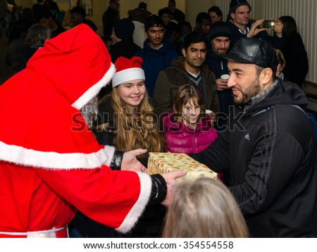 SCHARNHAUSEN, GERMANY - DECEMBER 20, 2015:: Refugees from Libya, Nigeria, Afghanistan, Pakistan, Eritrea, Gambia, Togo, Algeria, Tunisia and other countries are receiving presents from Santa Claus