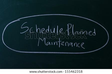 Schedule planned maintenance written with chalk on chalkboard - stock photo