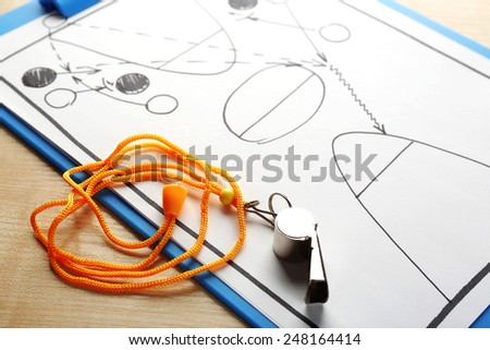Scheme basketball game on clip board paper with marker and wooden table background - stock photo
