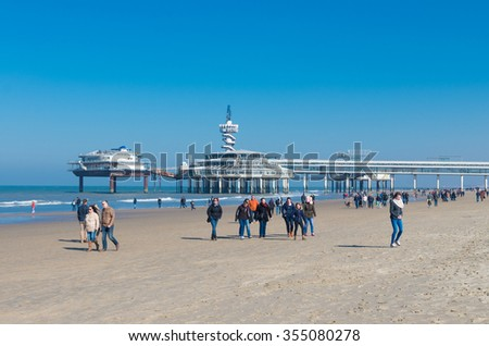 SCHEVENINGEN, NETHERLANDS - MARCH 8, 2015: Unknown people enjoying a sunny spring day on the North Sea beach. In the background the Scheveningen Pier. - stock photo