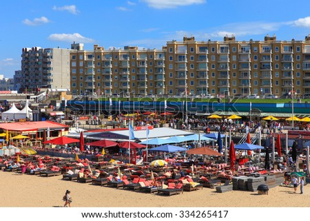 Scheveningen, The Netherlands - August 29, 2015: Locals and Tourists at Scheveningen's famous beach and seaside boardwalk, known for it's restaurants and shops.