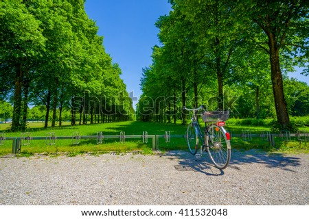 Schleissheim, Germany - July 30, 2015: Big green trees planted in perfect lineup creating an avenue of grass through the middle, bicycle parked and beuatiful blue sky