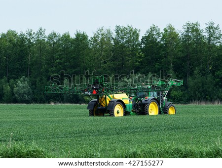 Schleswig Holstein, Germany, May 22, 2016: Tractor with sprayer during application of pesticides on May 22th, 2016