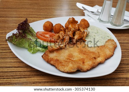 Schnitzel (german cutlet or escalope) with fried chanterelles and potato croquettes                                - stock photo