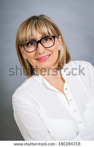 Scholarly attractive middle-aged blond woman in glasses standing looking at the camera with folded arms against a grey background