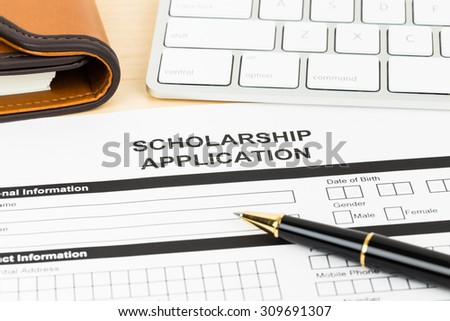 Scholarship application form with keyboard and pen
