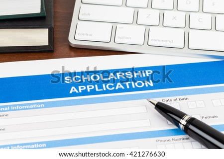 Scholarship application form with pen, keyboard, and text book - stock photo