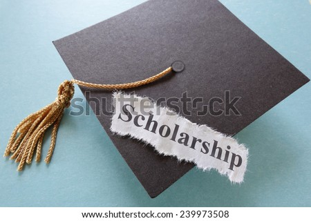 Scholarship paper note on a graduation cap                                - stock photo