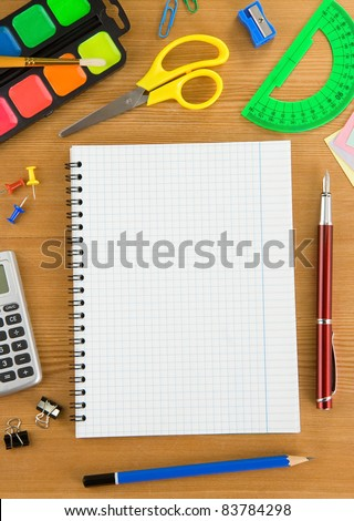 school accessories and checked notebook on wood texture - stock photo