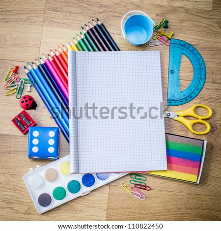 school accessories and checked notebook on wooden table - stock photo