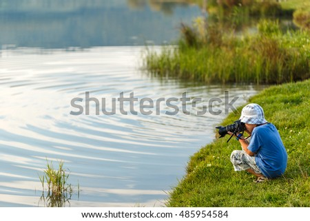 School-age boy photographing lake, taking a picture