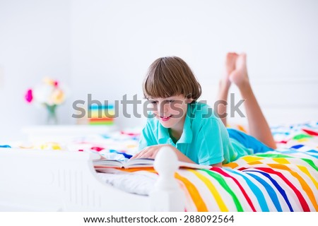 School age boy reading a book in bed. Children read books. Kids learning. Student kid doing homework in a sunny bedroom. Colorful textile bedding for child room. Smart students learn and study at home - stock photo