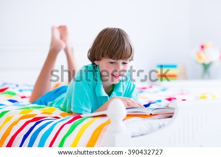 School age boy reading a book in bed. Children read books. Kids learning. Student kid doing homework in a sunny bedroom. Colorful textile bedding for child room. Smart students learn and study at home