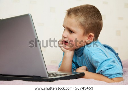 School-age boy sitting in front of the monitor laptop at home on the couch. - stock photo