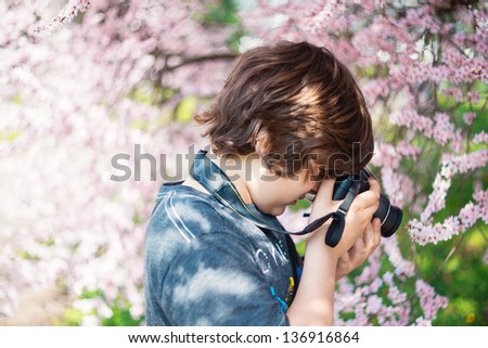 School-age boy with a camera photographs the cherry blossoms - stock photo