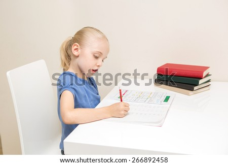 School Age girl with blond hair studying on white table against white table.   - stock photo
