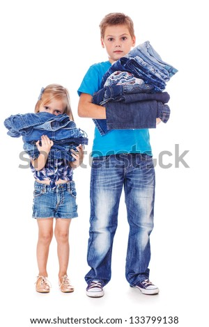 School aged boy and preschool girl holding jeans clothing in hands - stock photo