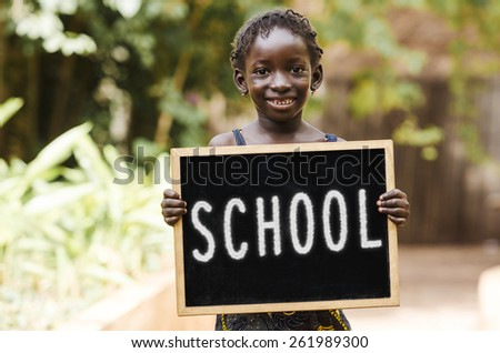 School And Education - African Girl Holding Chalkboard. An African girl holding a blackboard. - stock photo