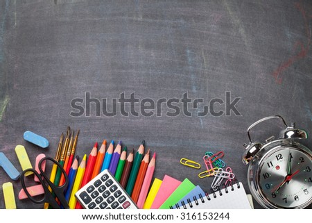 School and office supplies on blackboard background. Top view with copy space - stock photo