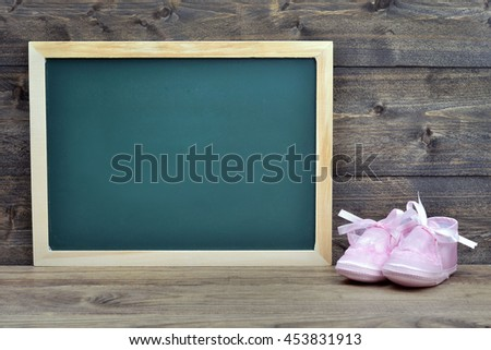 School board and kid shoes on wooden table