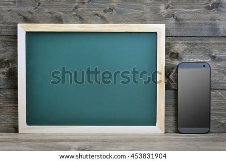 School board and smartphone on wooden table