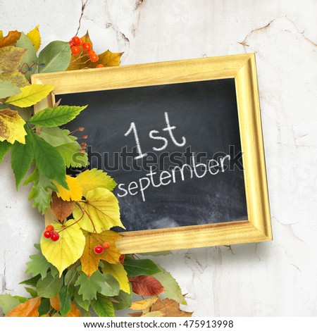 "school board with the inscription ""First September"" and a bouquet of autumn leaves on wooden background. School background"