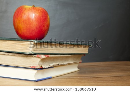 school books and apple against blackboard - stock photo