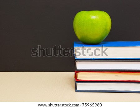 School books with apple on desk, on black school board background - stock photo