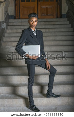 School boy.  A young dark skin, 18 years old student, wearing black fashionable blazer, pants, leather shoes, holding laptop computer, standing on stairs outside office, confidently looking at you. - stock photo