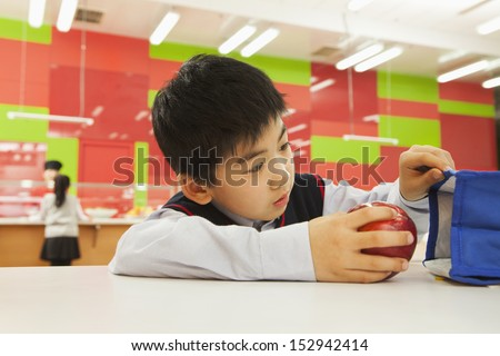 School boy checking lunch bag in school cafeteria - stock photo